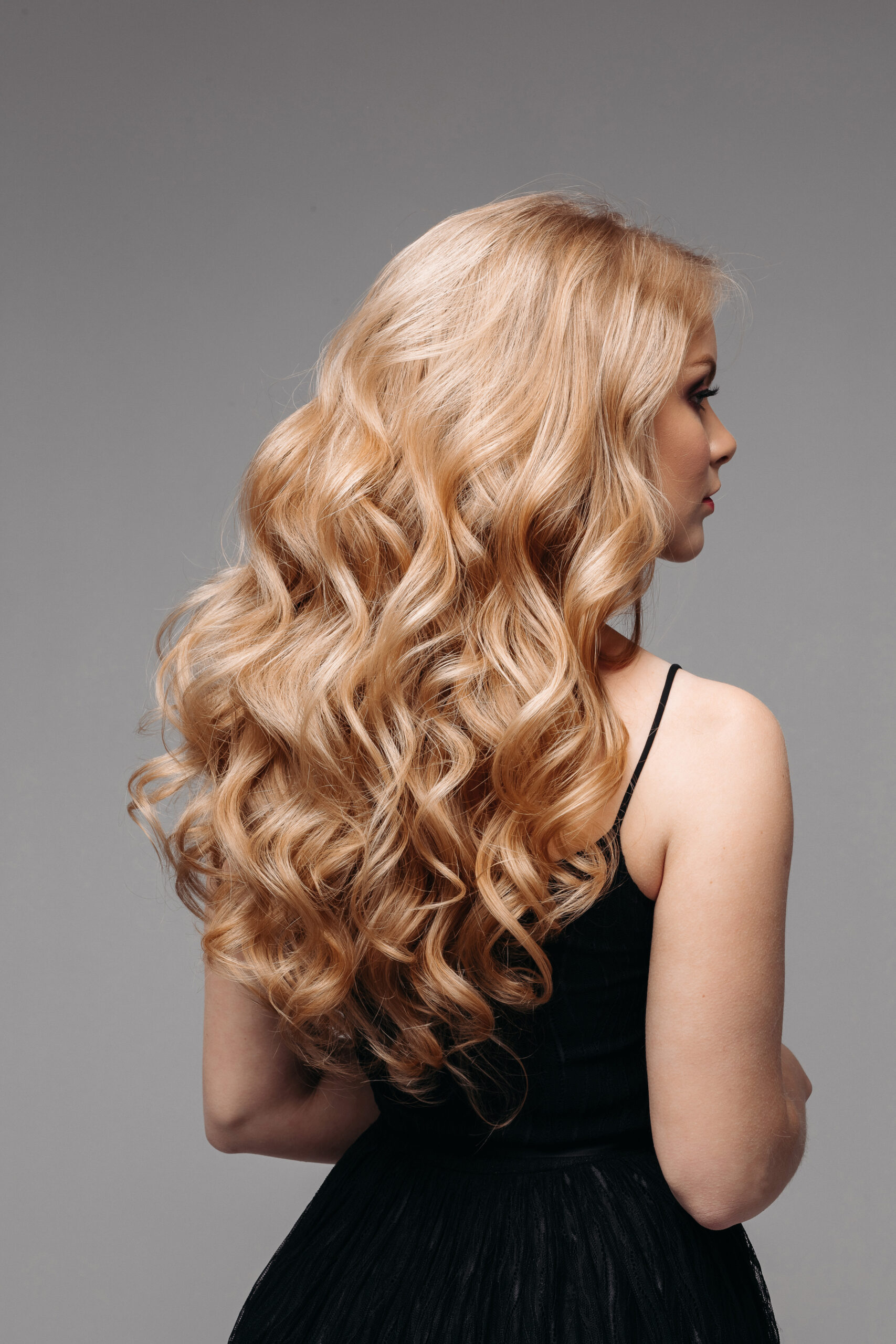 Back view of unrecognizable woman in black with volumous, blonde wavy hair over grey background. Isolated on grey. Studio. Perfect healthy hair. Hairdresser.