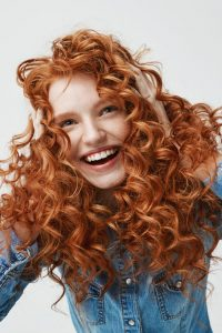 Portrait of cute happy girl laughing touching her curly red hair over white background.